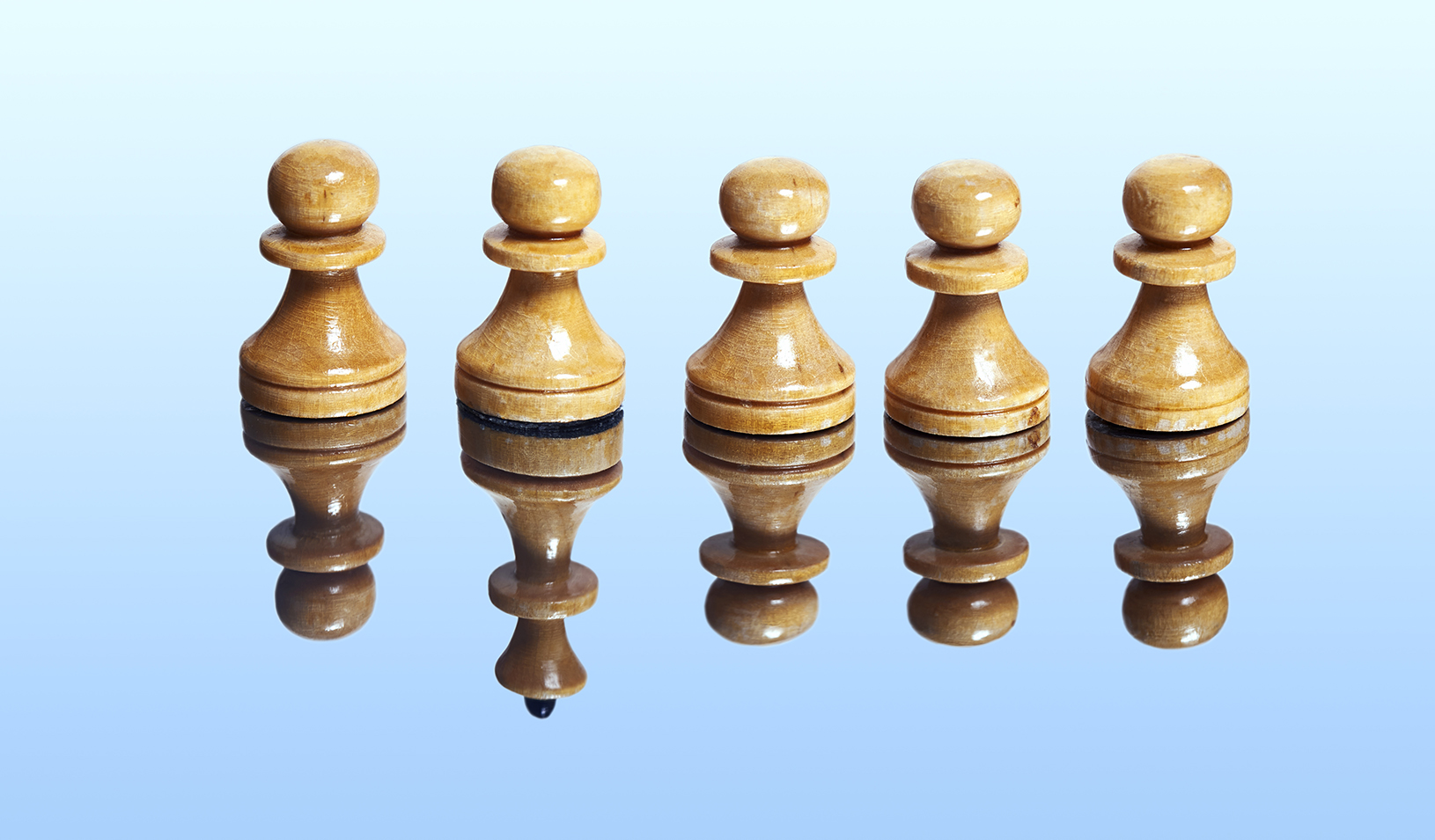 A photo-illustration showing a row of chess pawns, but in the reflective surface they sit on, you can see that one is really the queen. Credit: iStock/nikamata