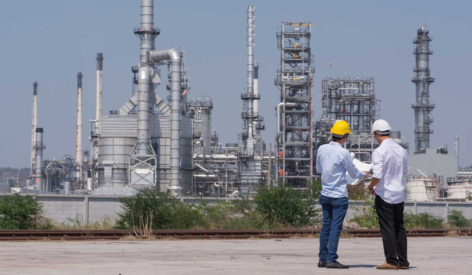 A photo of mechanical engineers working in an oil refinery. Credit: iStock/cofotoismei