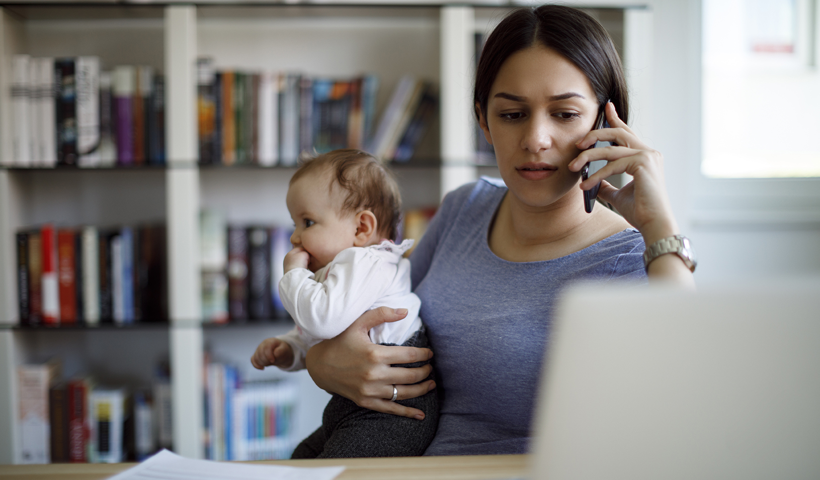 Stressed mother using mobile phone and laptop at home. Credit: iStock/damircudic