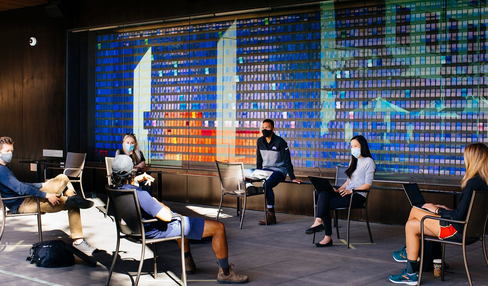 Students, masked and distanced, study together in front of the color wall during fall quarter, 2020. Credit: Elena Zhukova