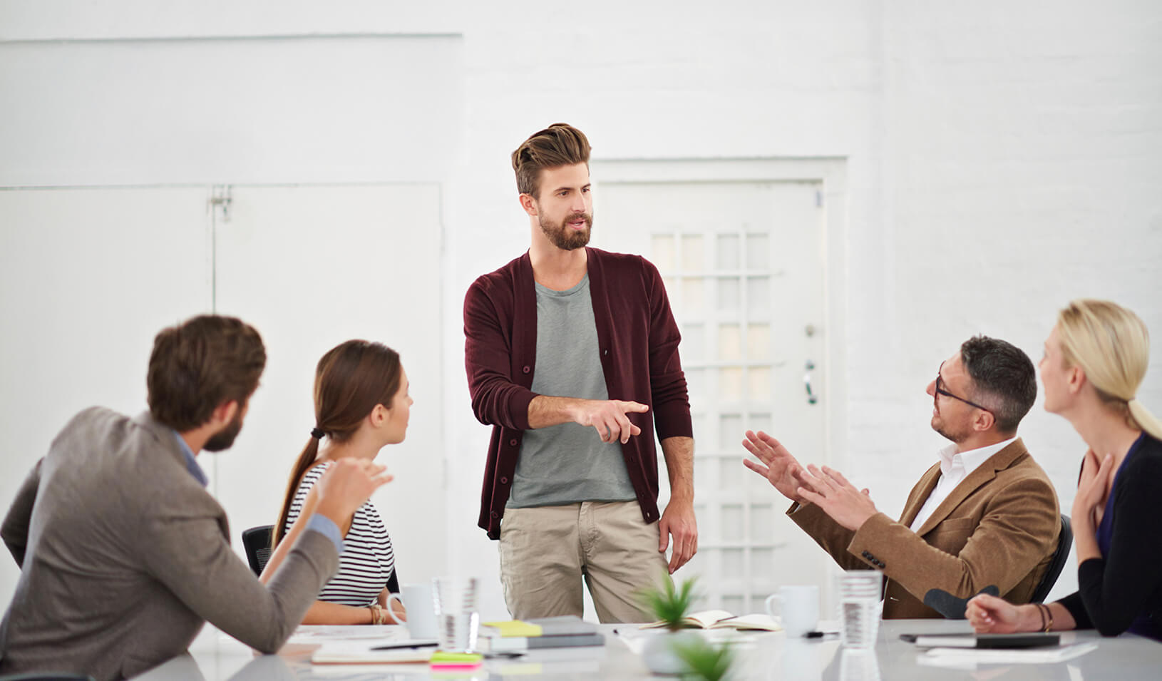 Twentysomething hipster standing while talking to a group of seated meeting participants | iStock/Yuri_Arcurs