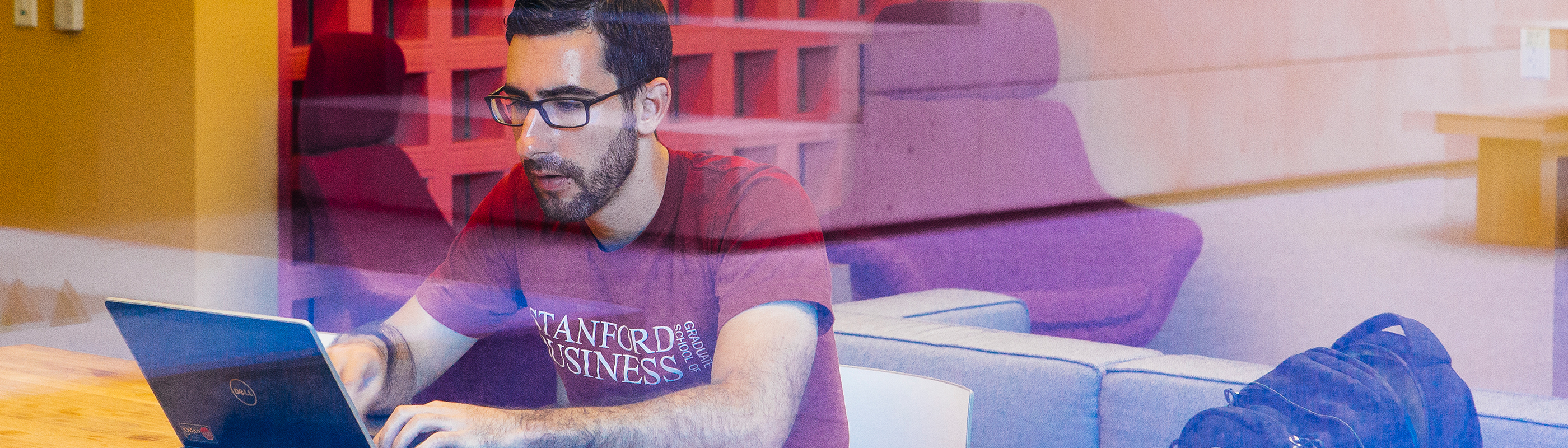 A man wearing a Stanford GSB t-shirt and working on a laptop in Bass Library