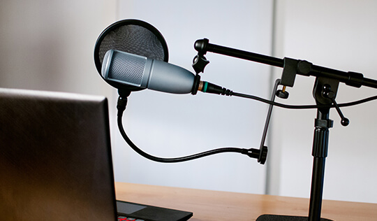 Recording microphone set up in front of a laptop.