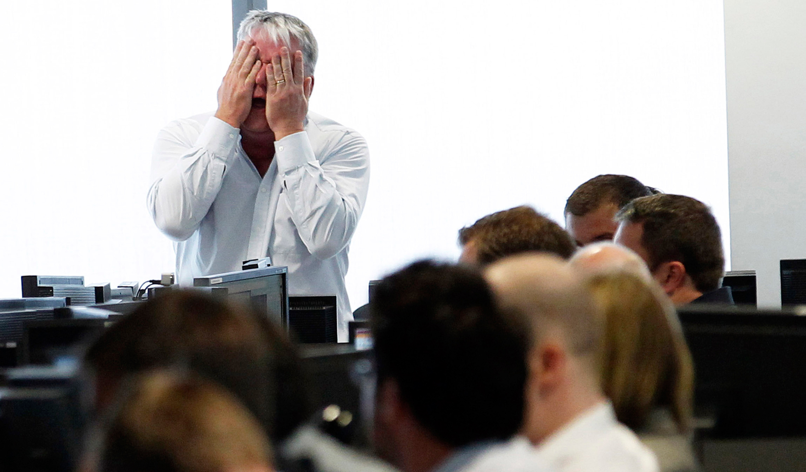 A man holding his hands over his face at work. | Reuters/Luke MacGregor