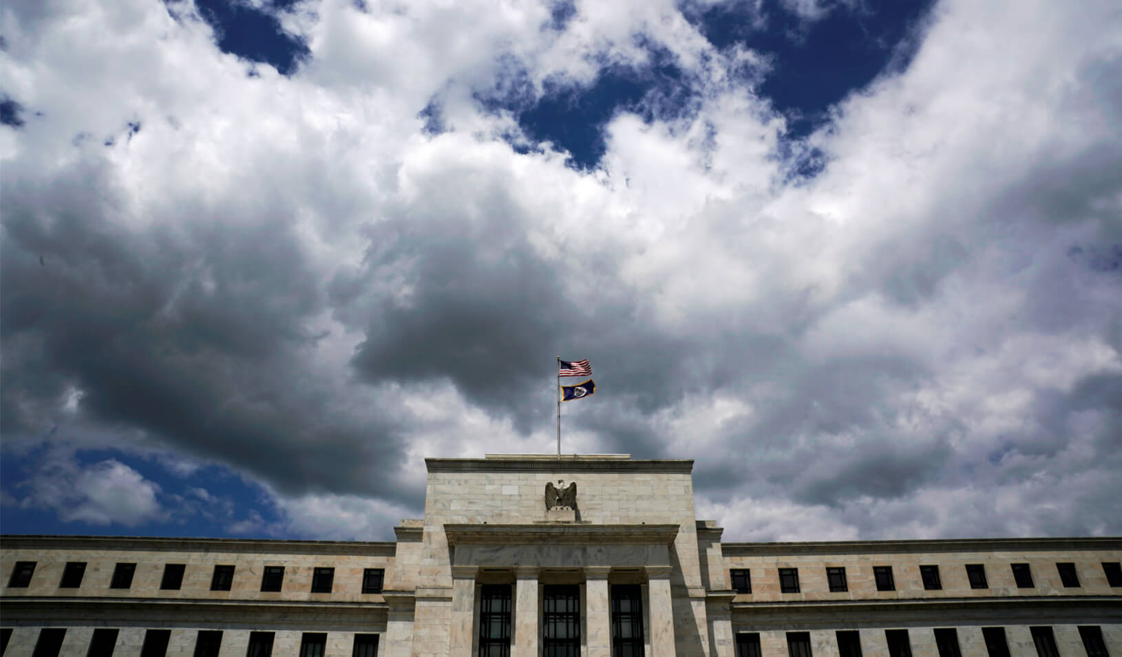 Flags fly over the Federal Reserve Headquarters in Washington. Credit: REUTERS/Kevin Lamarque