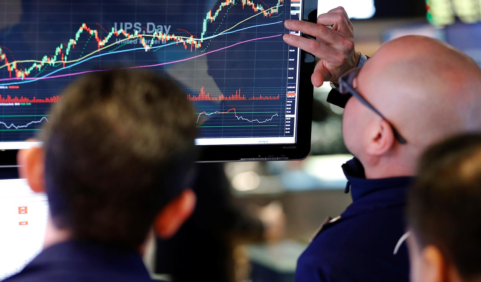 Traders examine stock charts