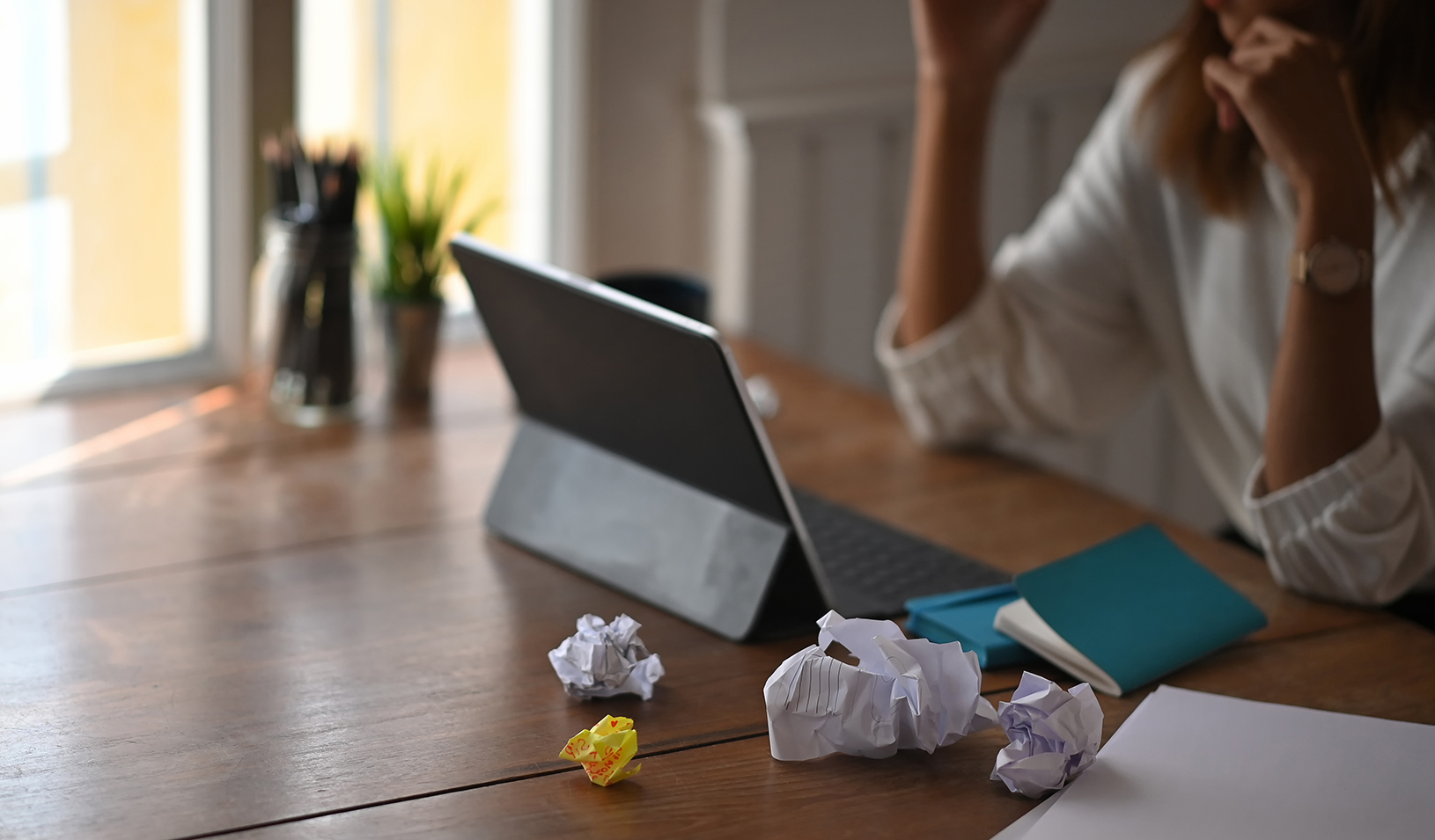 Woman sits at table looking at tablet, with crumpled papers around her, feeling stressed. Credit: iStock/PrathanChorruangsak