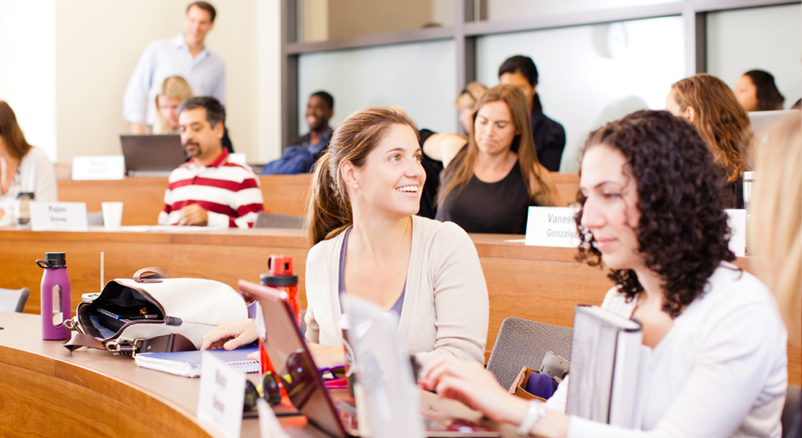 Female student in class talking with someone behind her