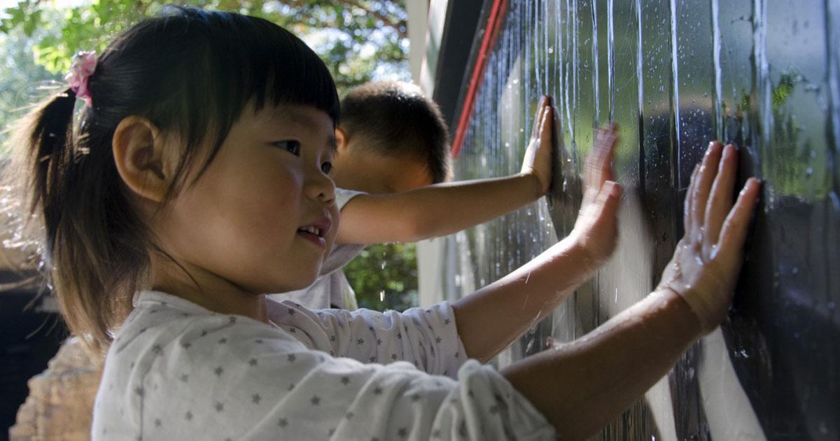A little girl plays with and learns about water as it trickles down the wall.
