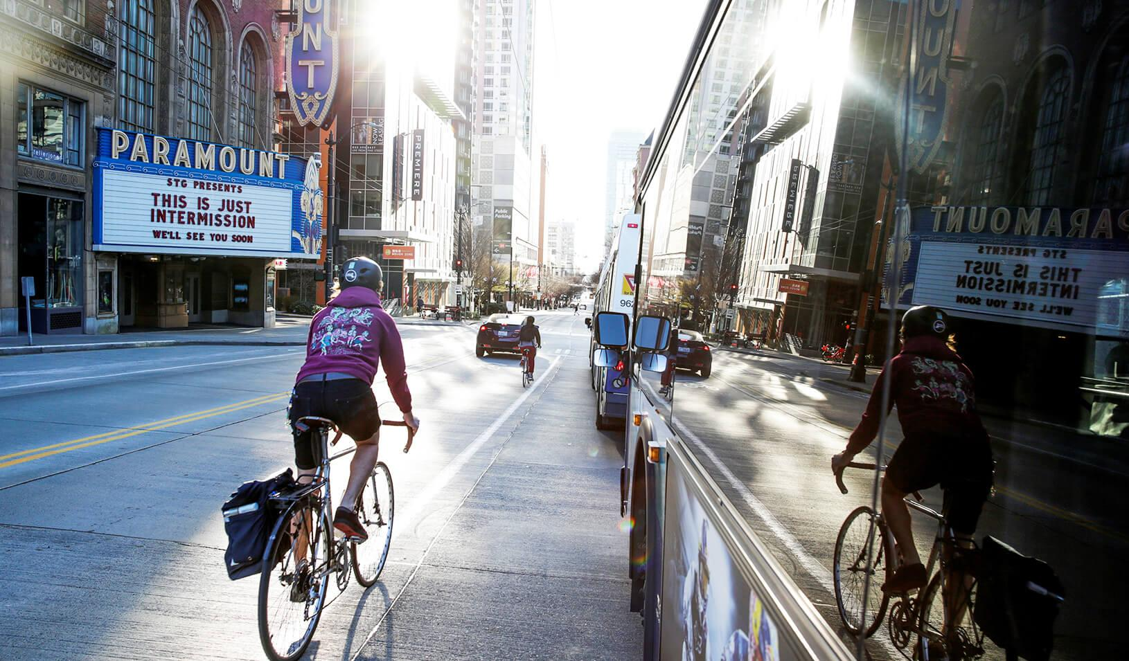 "A cyclist rides down a city street past the Paramount Theater whose marquee reads: ""This is just intermission, we'll see you soon."" Credit: Reuters/Jason Redmond"
