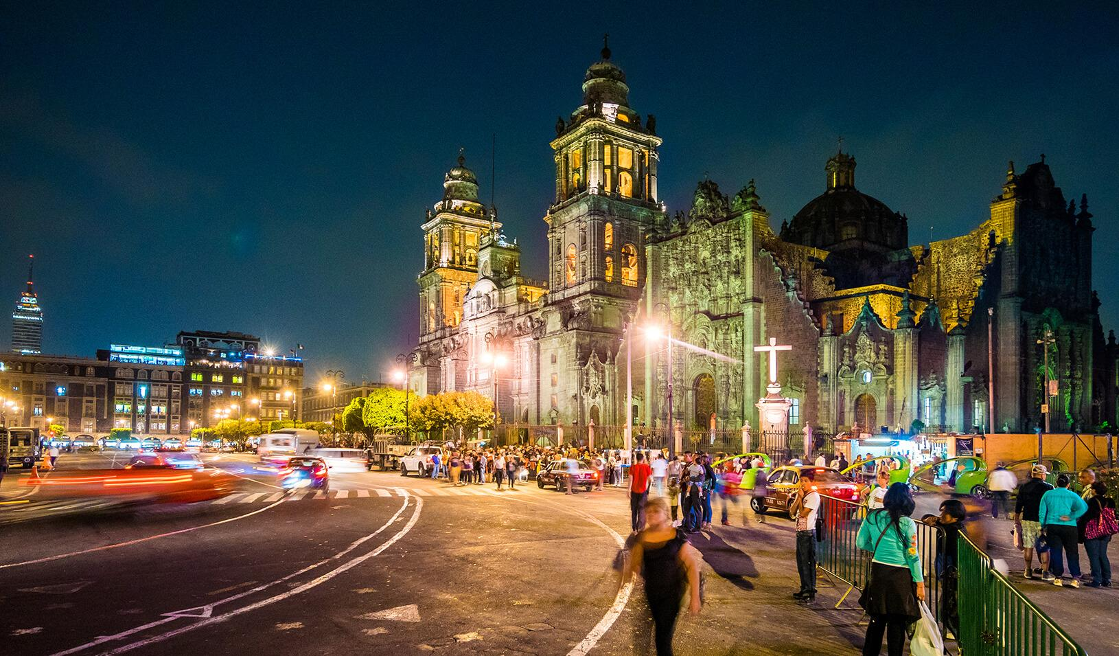 View of the busy street outside the Metropolitan Cathedral of the Assumption in Mexico City, Mexico at night.