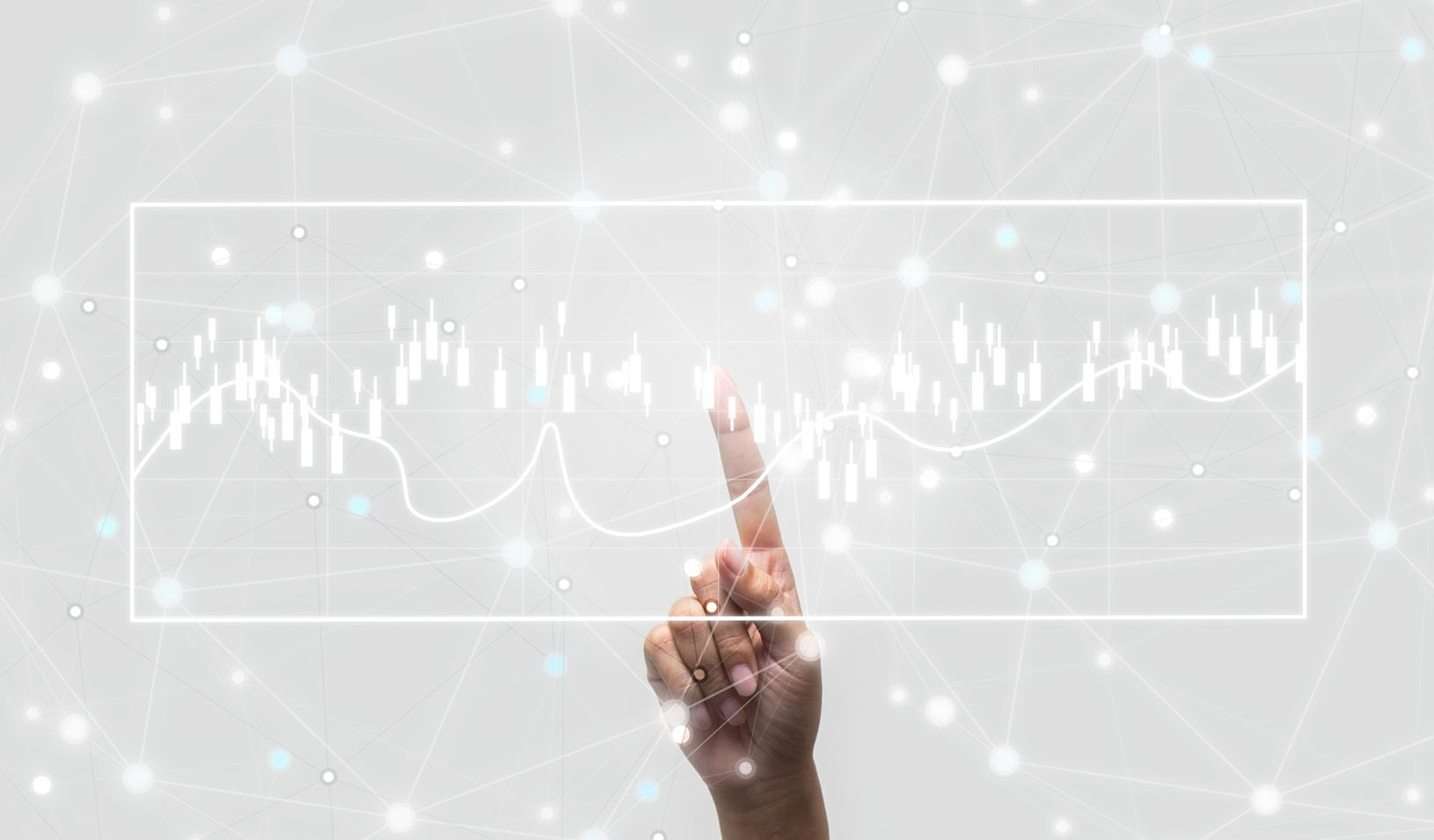 Future of financial business concept: Hand touching increasing graph with finance symbols coming. Credit: iStock/Yozayo
