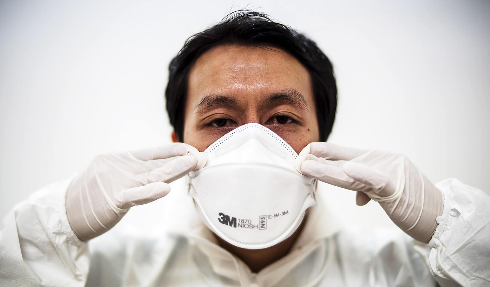 A doctor puts on his medical mask | Reuters/Athit Perawongmetha