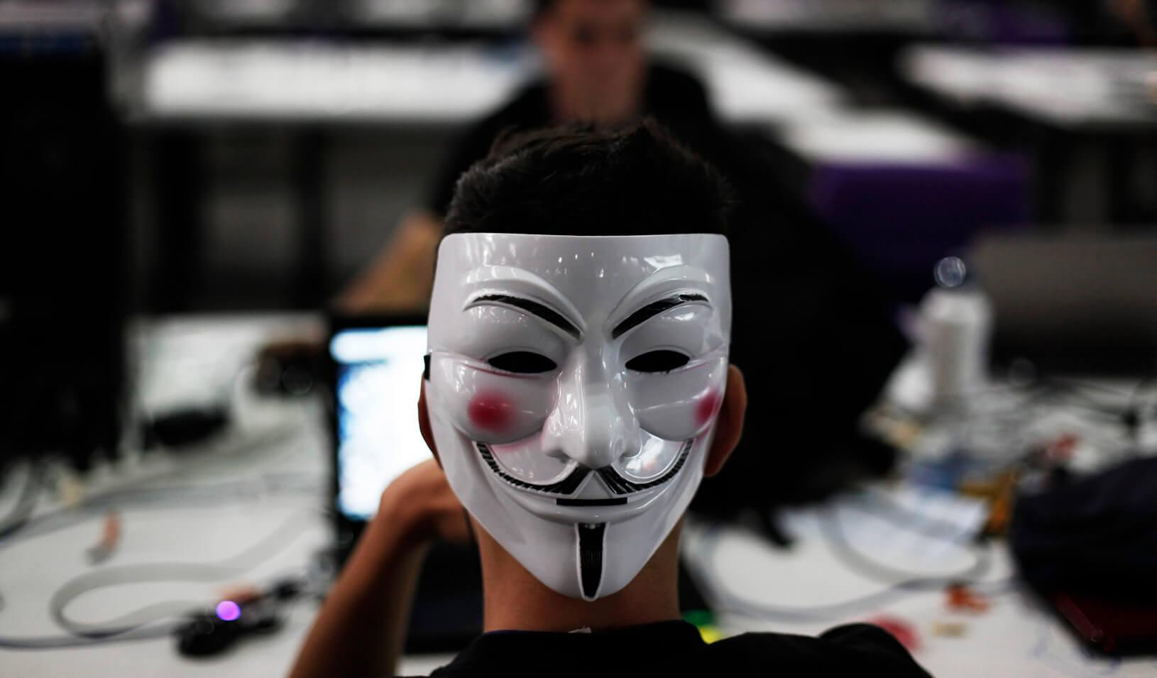 A man wearing a Guy Fawkes mask surfs the web