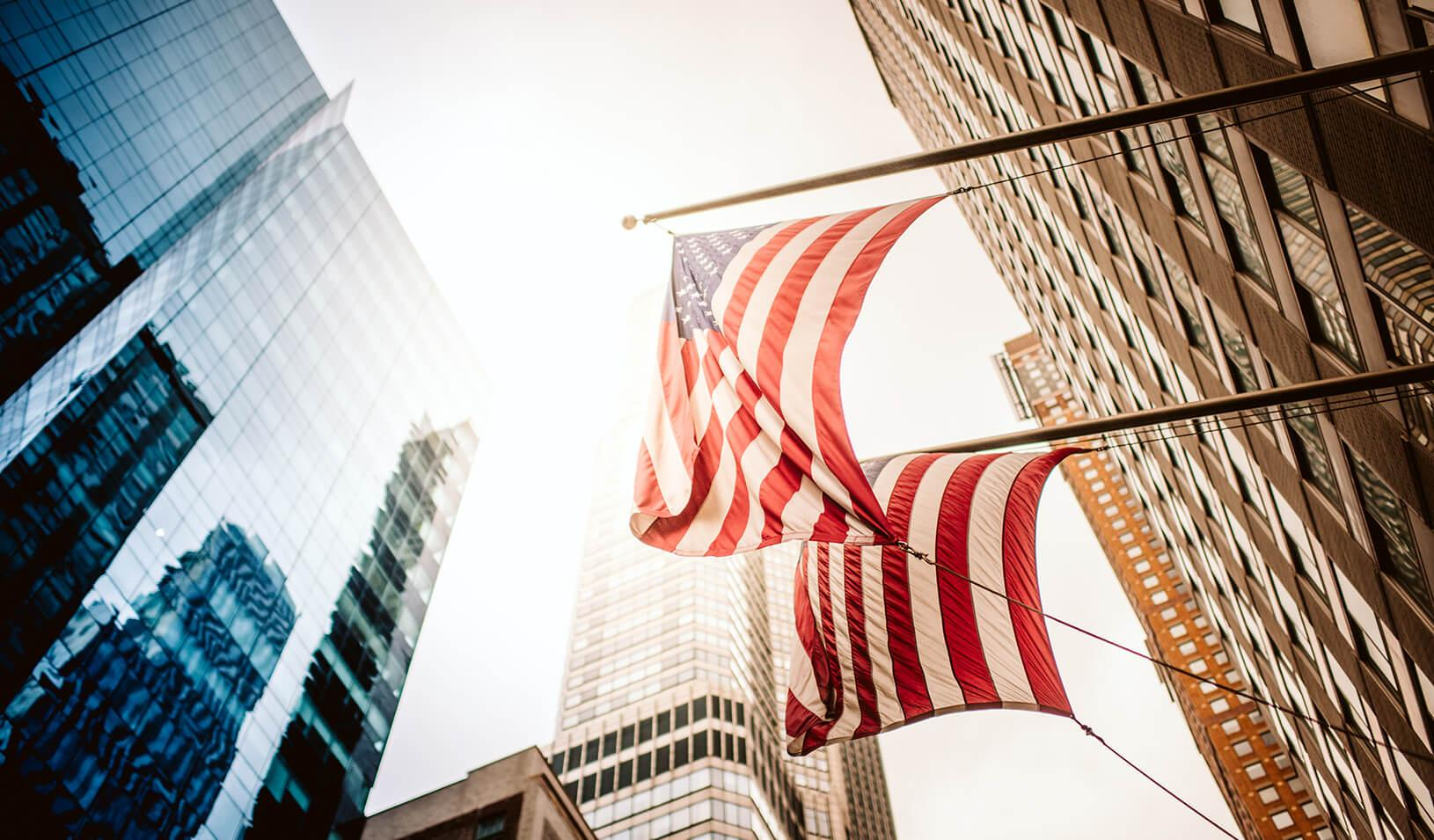 New York City office skyscraper with US Flags Reflection in the sunlight. Credit: iStock/PPAMPicture