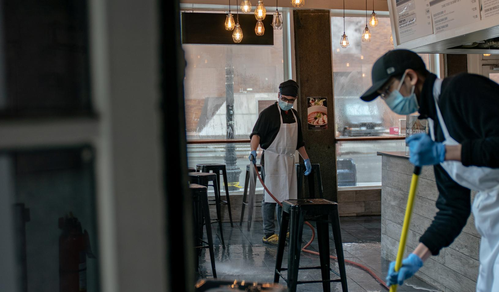 Restaurant staff clean the floor after closing early afternoon following the outbreak of coronavirus disease (COVID-19), in New York City, U.S., March 16, 2020. Credit: REUTERS/Jeenah Moon