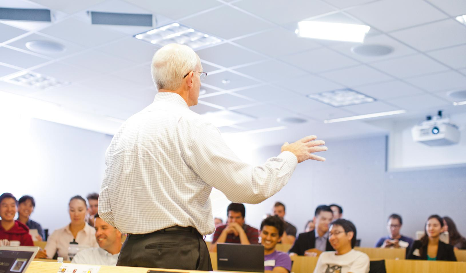 A faculty member speaking in front of class.