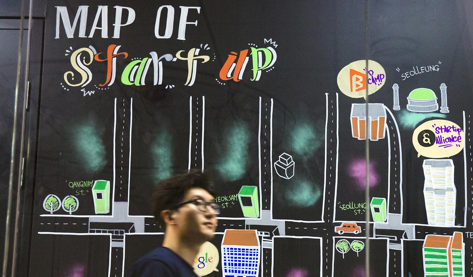 "Man walking past a wall painting labeled ""Map of Start-up"" at the Google Campus in the Gangnam district of Seoul."