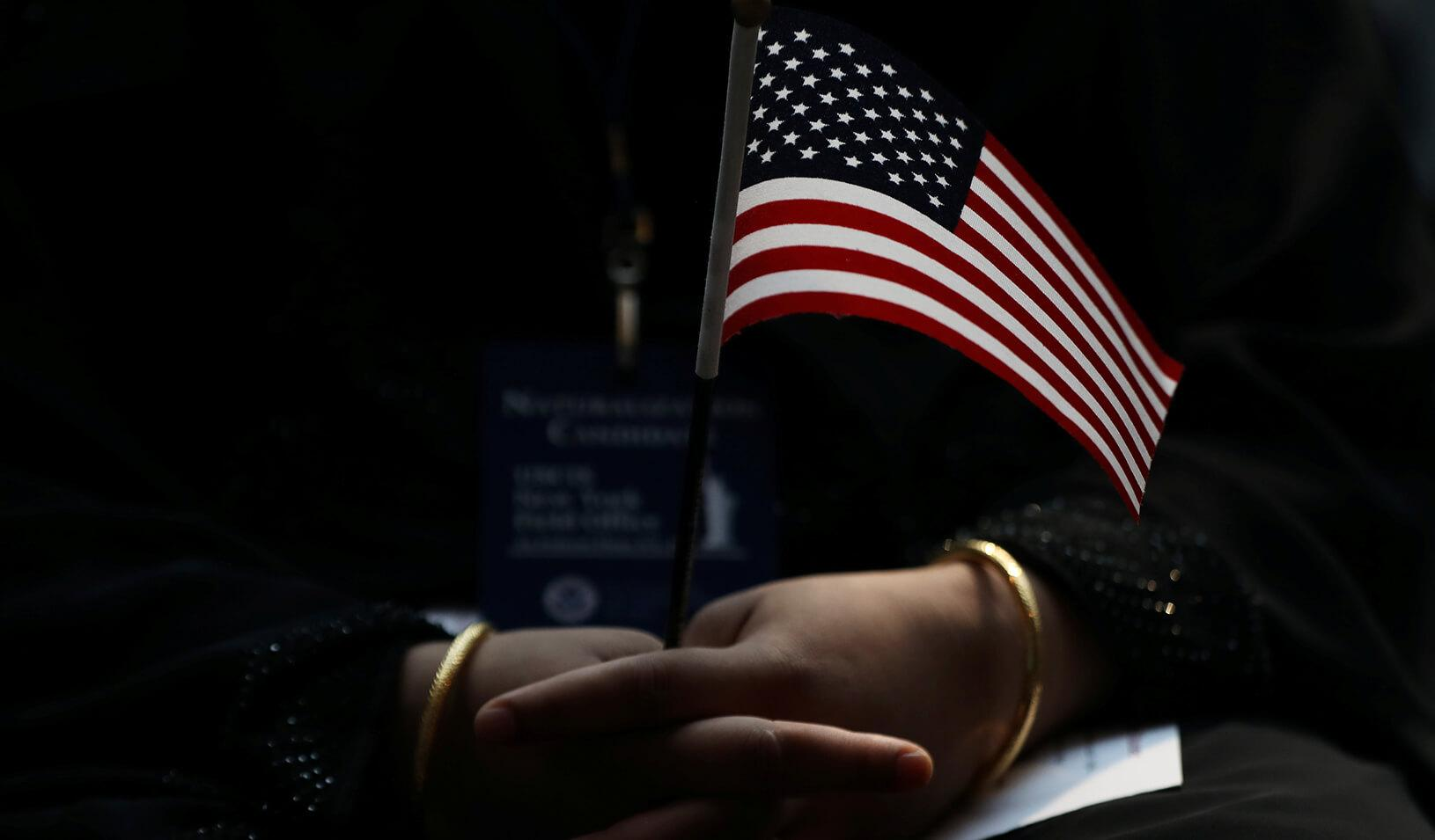 An immigrant woman holds a U.S. flag during a U.S. Citizenship and Immigration Services Naturalization ceremony in the New York Public Library in New York.  Credit: REUTERS/Shannon Stapleton