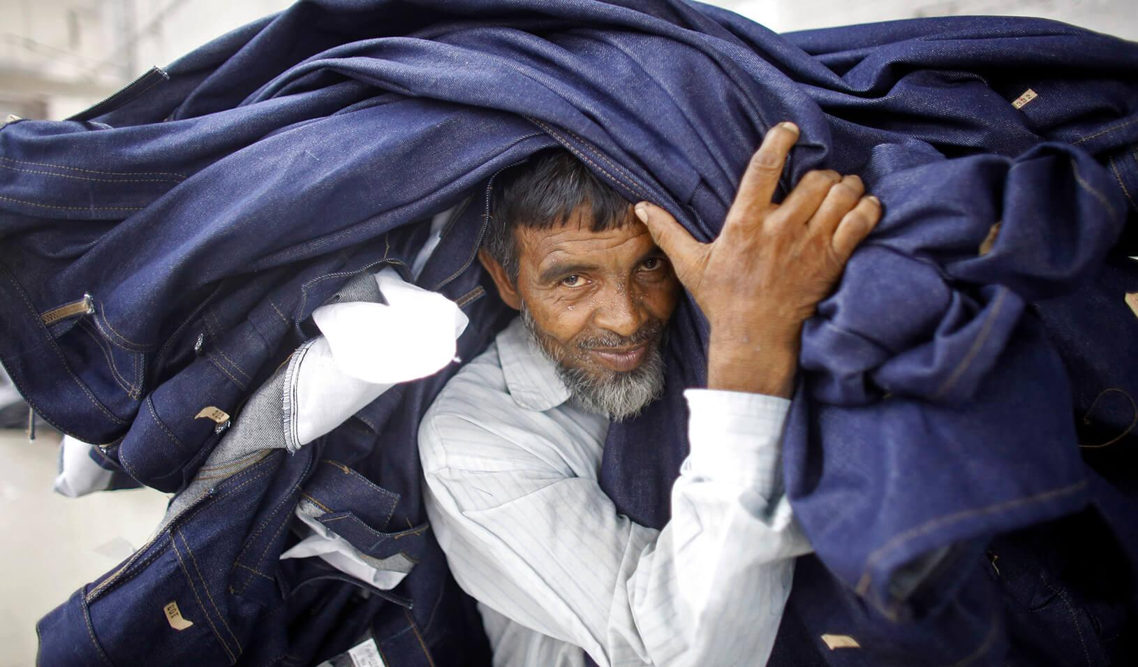 A worker carries a stack of clothes in a garment factory