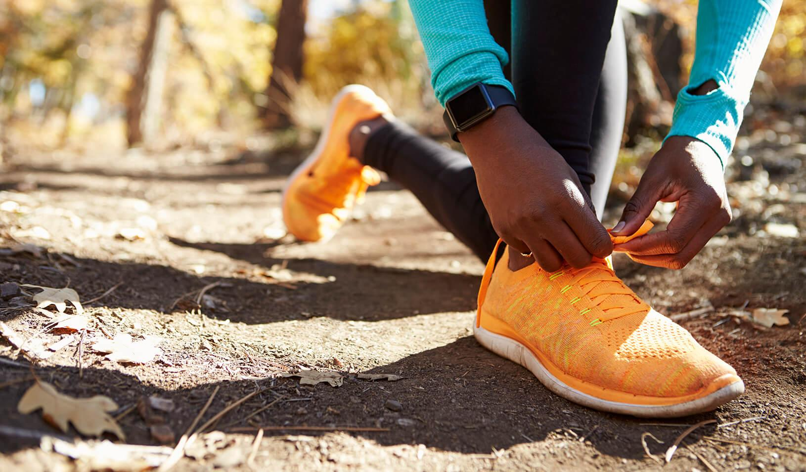 A woman runner wearing a fitness tracker stops to tie her shoe | iStock/monkeybusinessimages