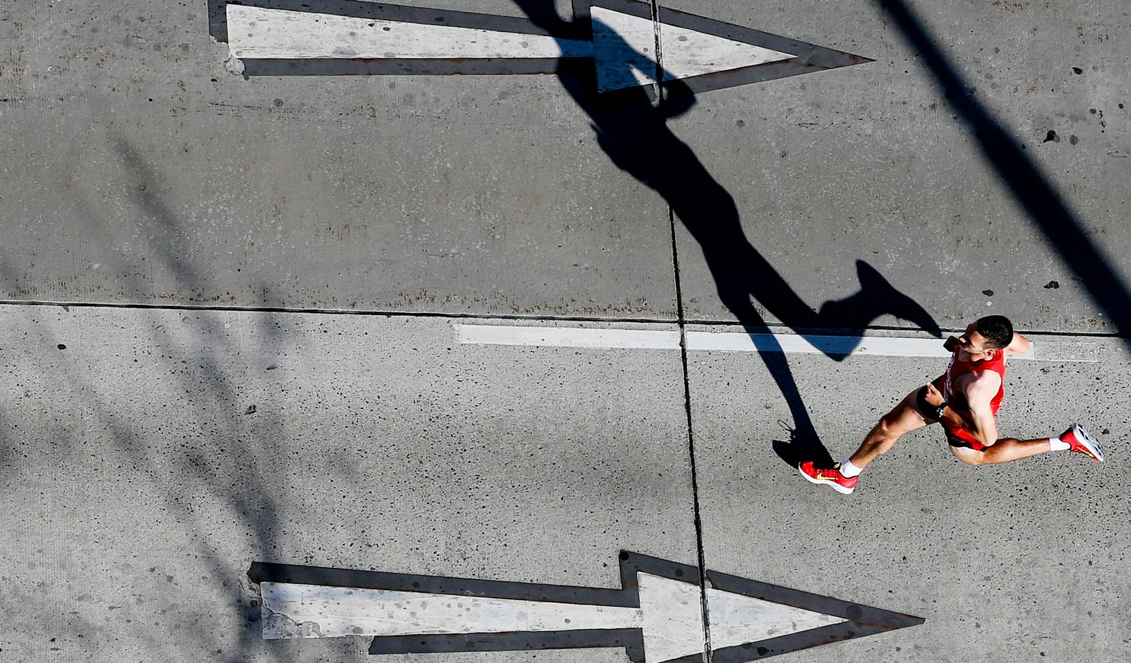 A runner going the opposite direction of arrows on the road