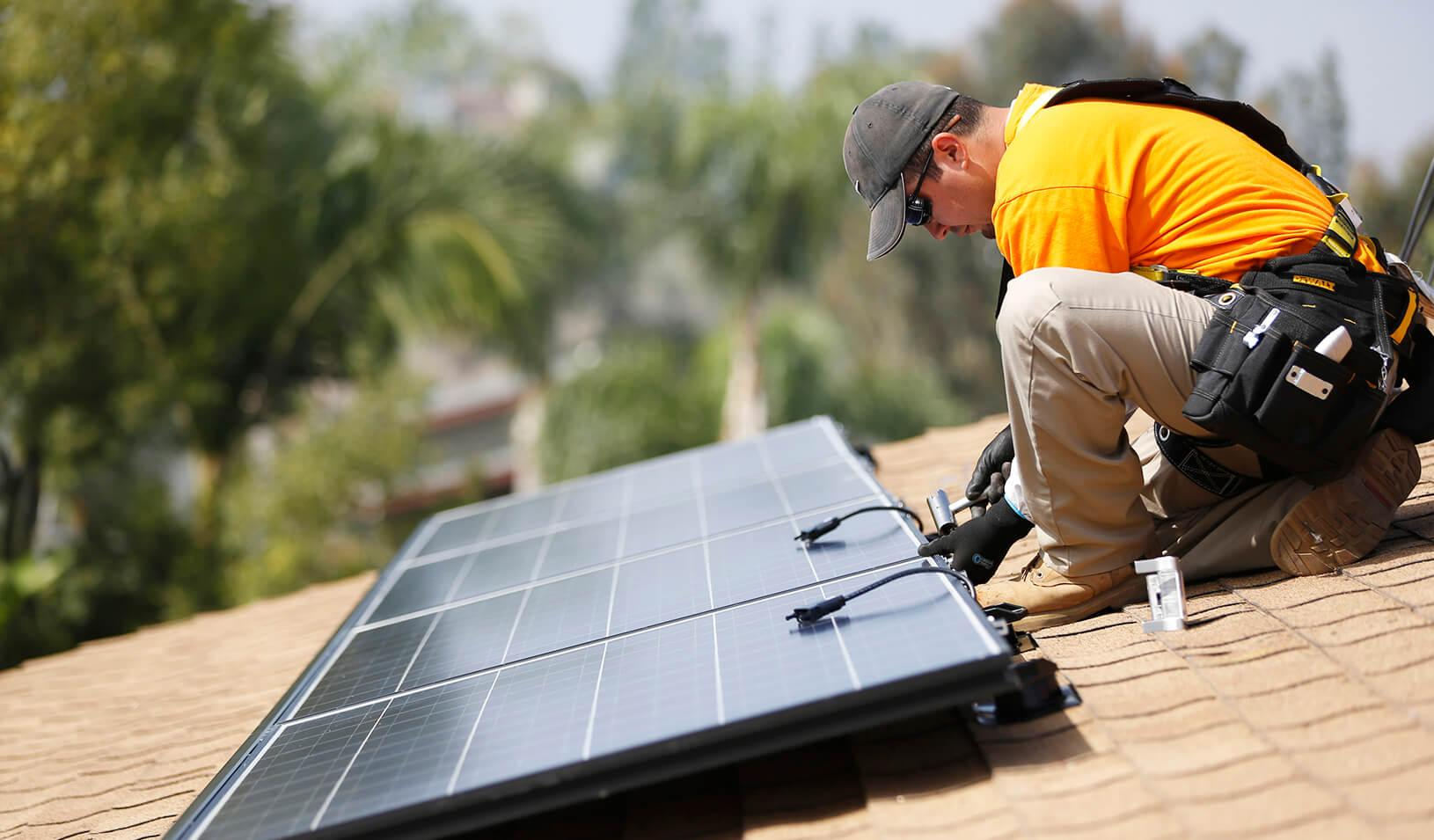 A solar technician installs panels on the roof of a house