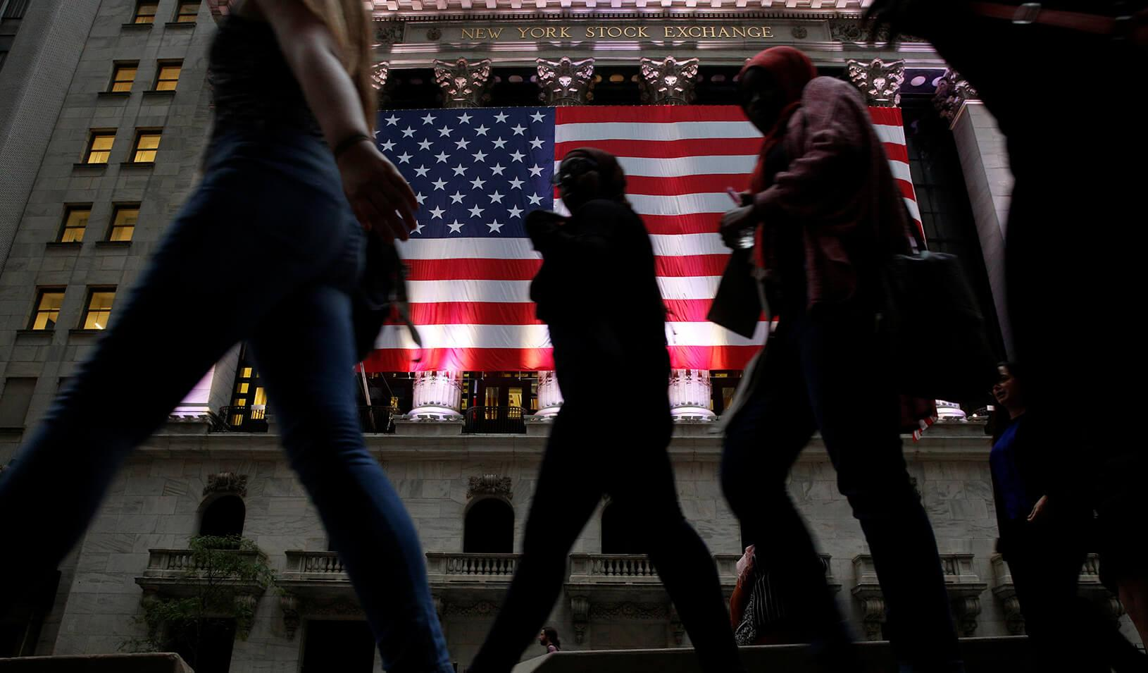 People pass by the New York Stock Exchange (NYSE) in the financial district in Manhattan borough of New York City.