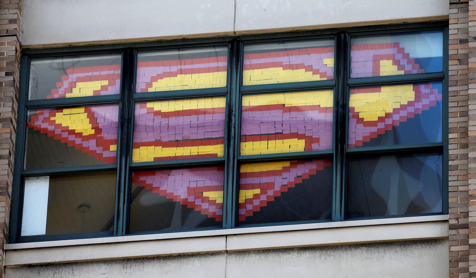 Superman's logo created using sticky notes in a window