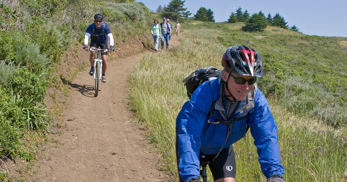 A mountain biker smiles as she rides down a hill.