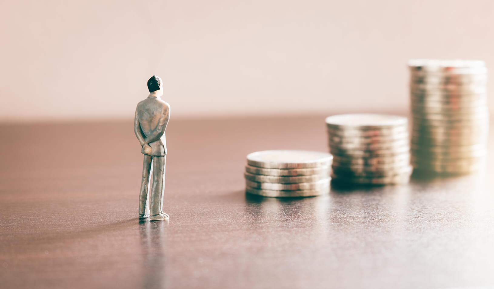 A small figure stands facing 3 piles of coins, in increasing value   iStock/wutwhanphoto