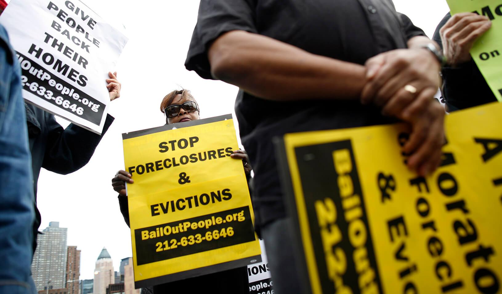 People protest outside the entrance for the Real Estate Disposition Corp Foreclosure Home Auction in New York, March 8, 2009. The auction of foreclosed homes in New York City on Sunday drew protesters who blamed banks for an epidemic of home losses and ca