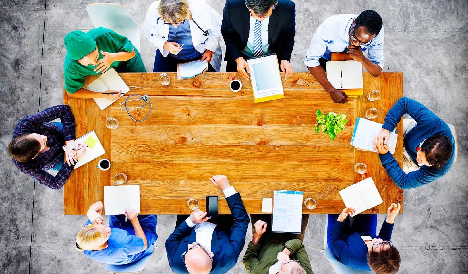 Doctors conduct a meeting around a conference table