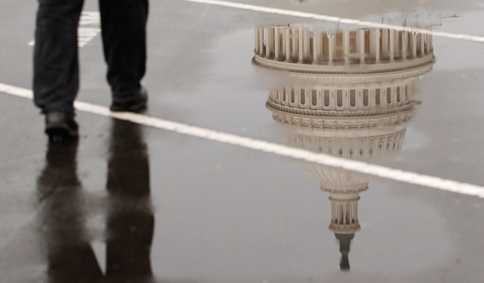 The dome of the U.S. Capitol Building is reflected in a puddle on a rainy morning. Credit: Reuters/Kevin Lamarque