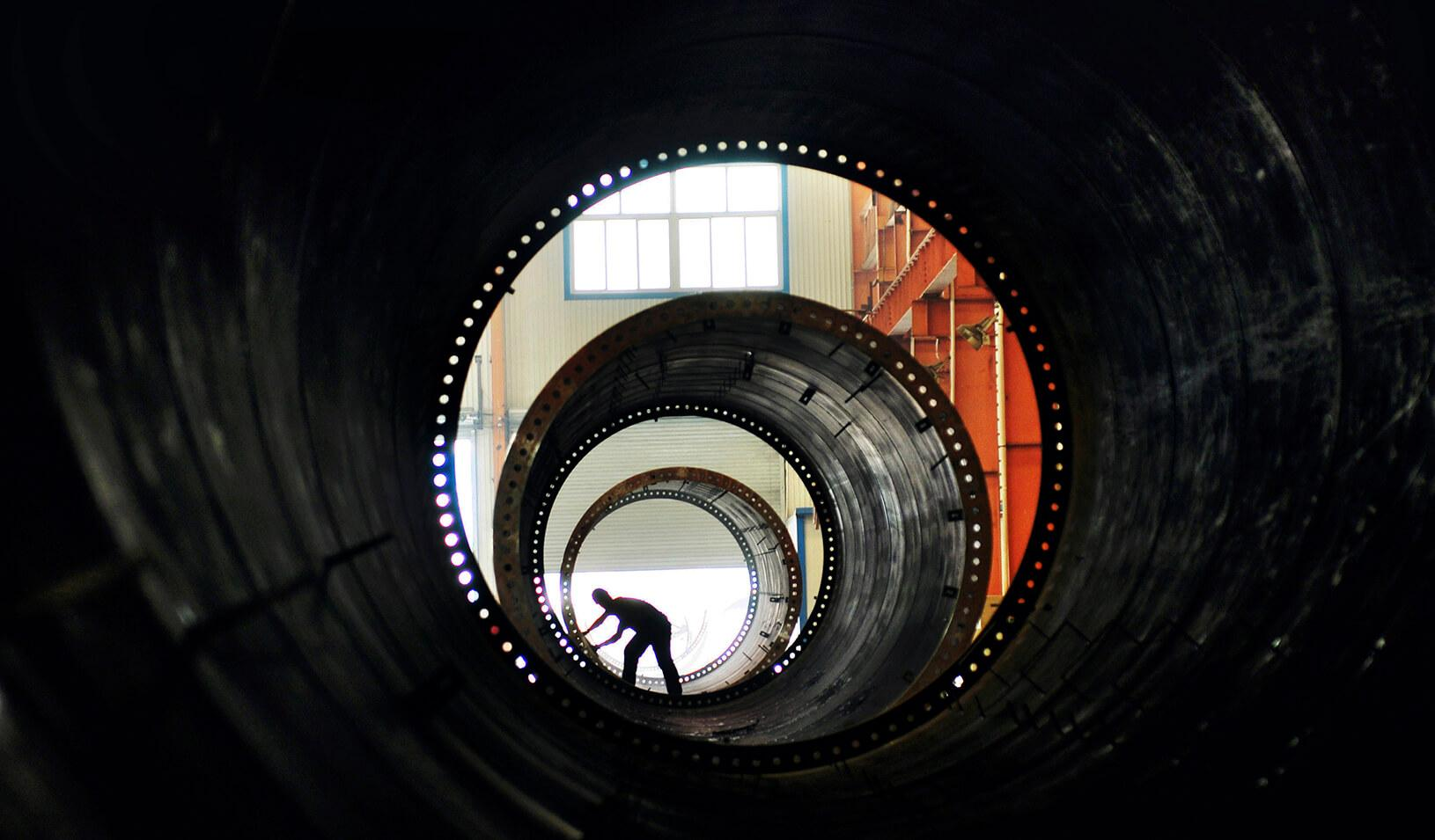 A laborer builds components of wind turbines at a wind power equipment factory.