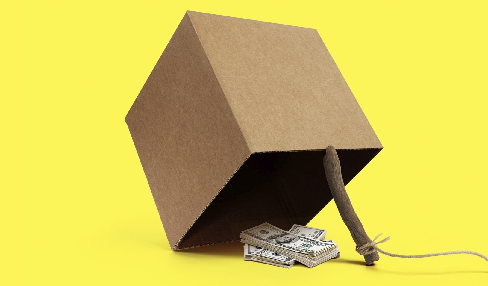 A photo illustration of a pile of money under a booby-trapped box. Credit: Alvaro Dominguez