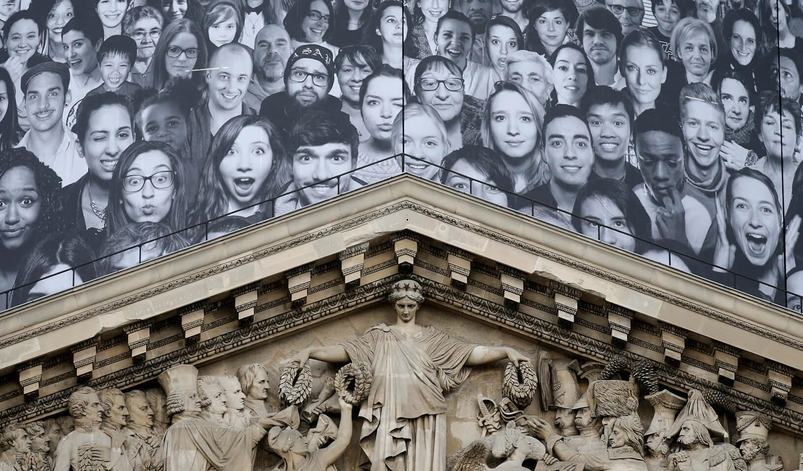 Portraits by contemporary artist JR are displayed on the worksite boarding placed around the dome on the Pantheon. Credit: Reuters/Christian Hartmann