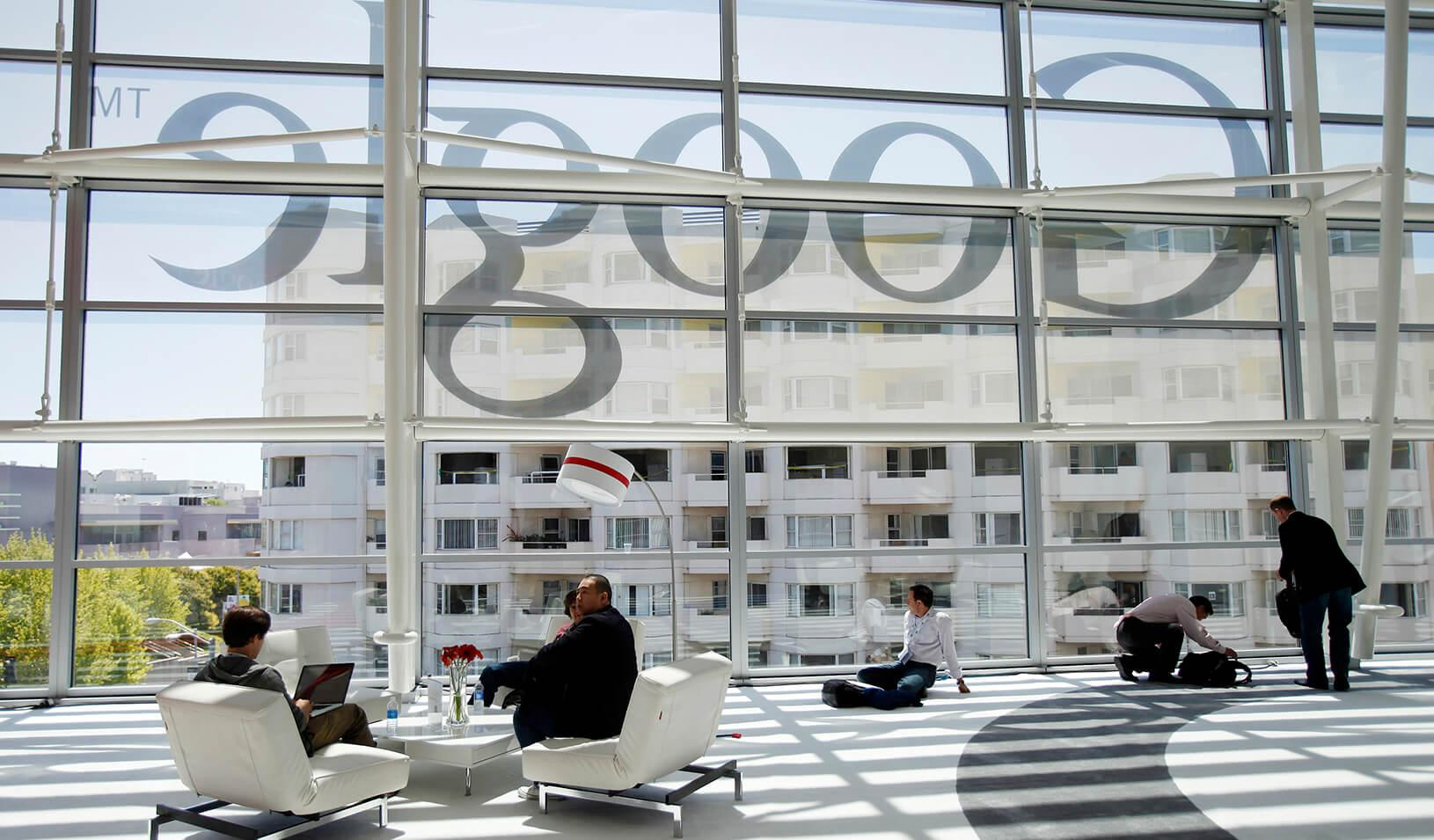 Men shown in the lobby with the Google logo reflected in the background. Credit: Reuters/Stephen Lam