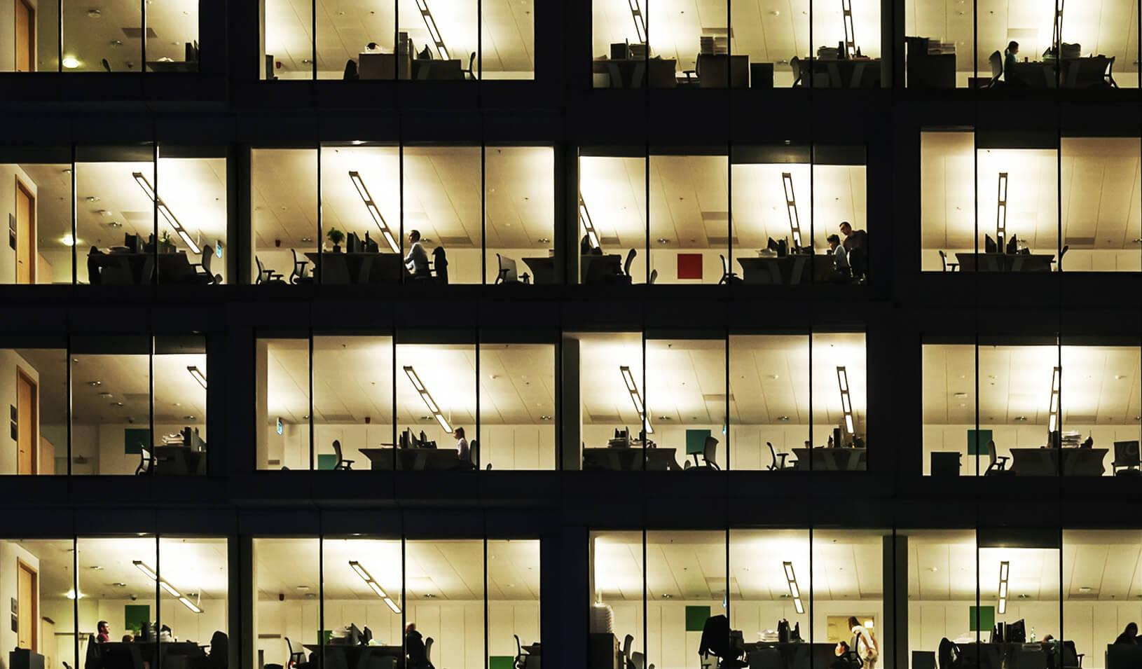 An office building at night showing people working late | iStock/Kilhan