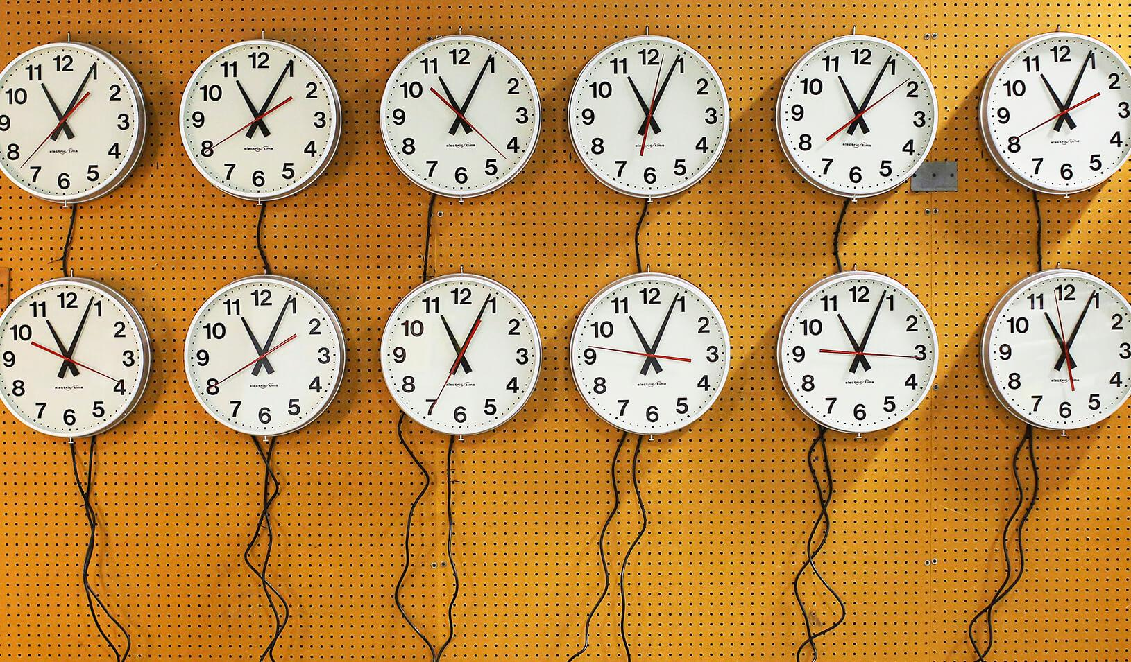 Twelve wall clocks close together. |