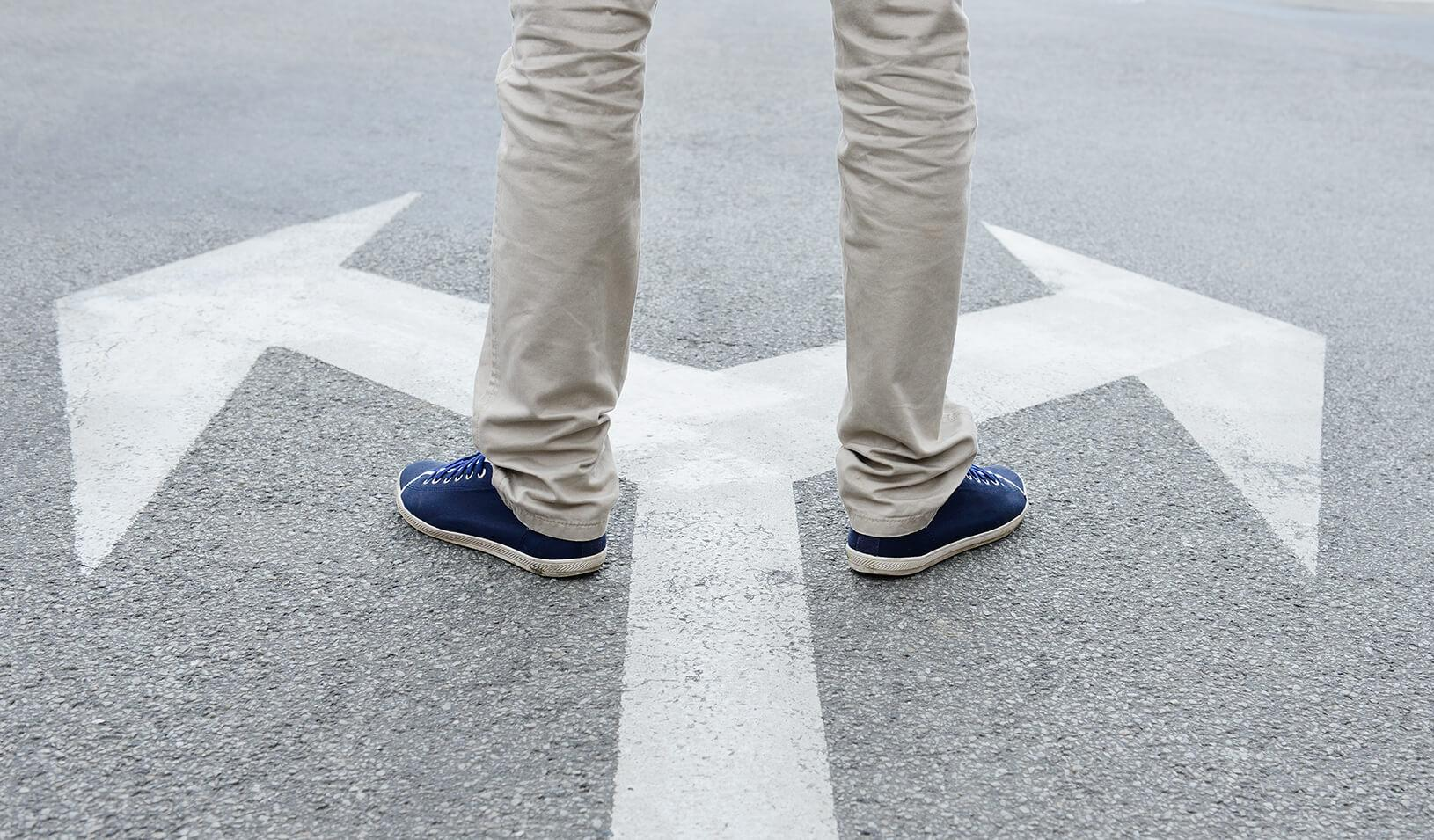 Person standing on directional arrows. | iStock/Olaser