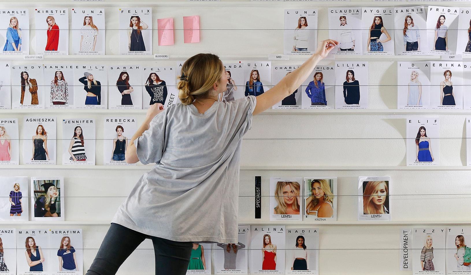 A woman arranges fashion photos