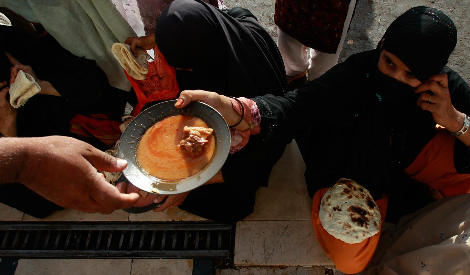 A woman handing a bowl of food to someone else