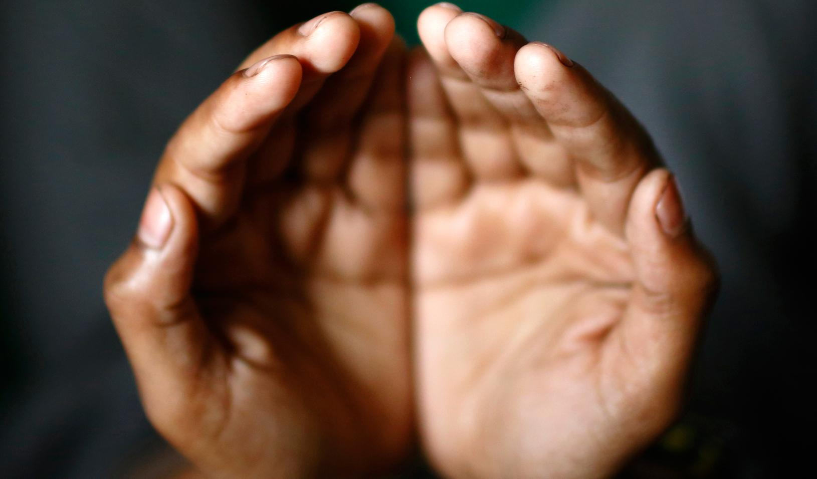 A person holding his or her hands together