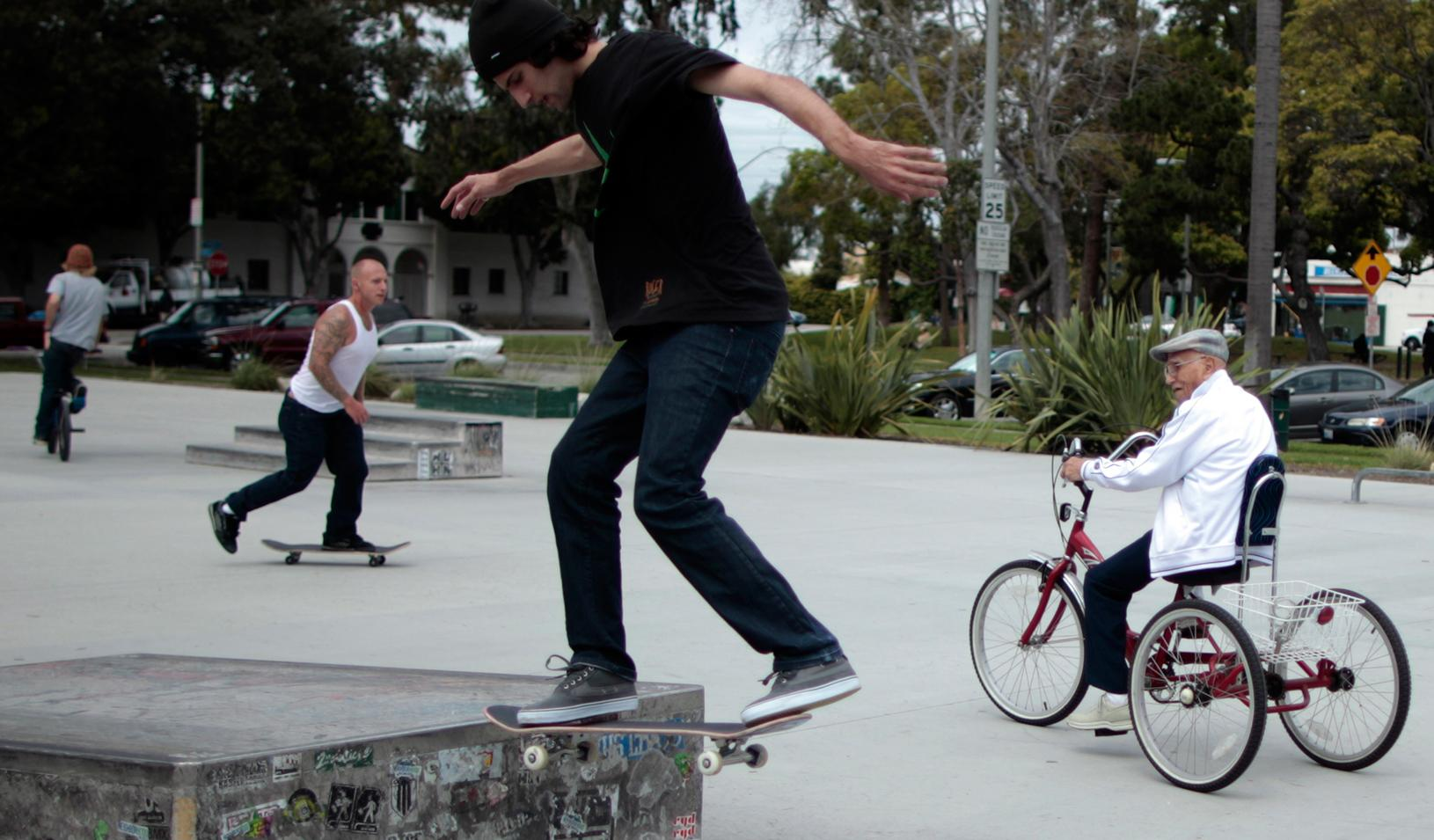 Young guys on skateboards and an older man on a bike