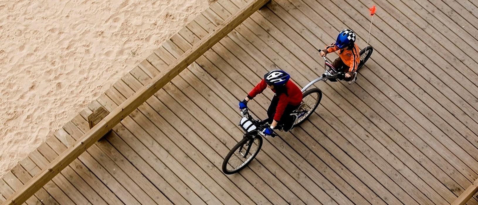 A child and parent riding a bicycle built for two along the beach