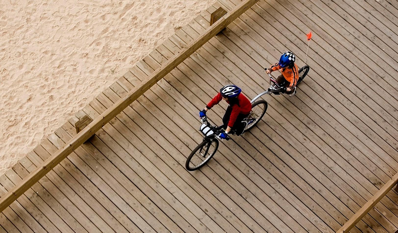 A parent and child ride a bicycle built for two along the beach