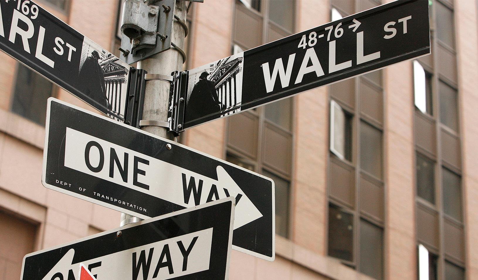 "Street signs that say ""Wall Street"" and ""One Way"""