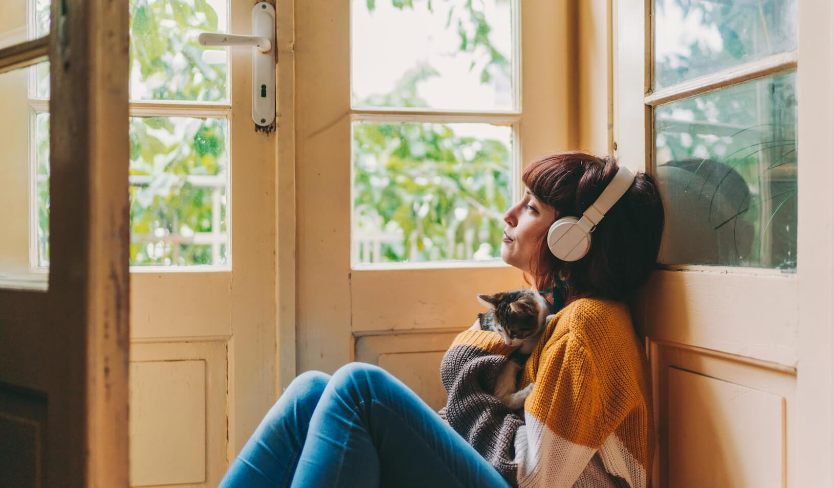 Woman cuddles cat and looks out the window while listening to a podcast in headphones. Credit: iStock/Martin Dimitrov