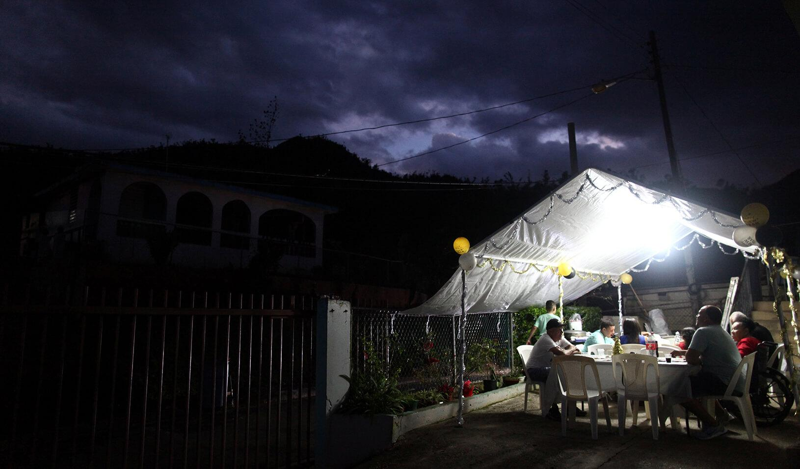 Residents of the El Salto neighbourhood share a meal during New Year's Eve after Hurricane Maria damaged the electrical grid in September, in Morovis, Puerto Rico December 31, 2017. | REUTERS/Alvin Baez